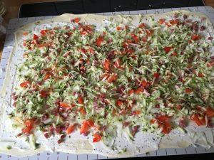 Teig ausrollen, mit Creme fraiche bestreichen und mit dem Gemüse belegen